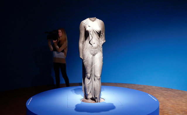 """A camerawoman takes pictures behind a statue during a media preview of the exhibition """"Osiris – Egypt's Sunken Mysteries"""", which features some 300 objects retrieved from the depths off Egypt's Mediterranean coast, at Museum Rietberg in Zurich February 9, 2017. (Photo by Arnd Wiegmann/Reuters)"""
