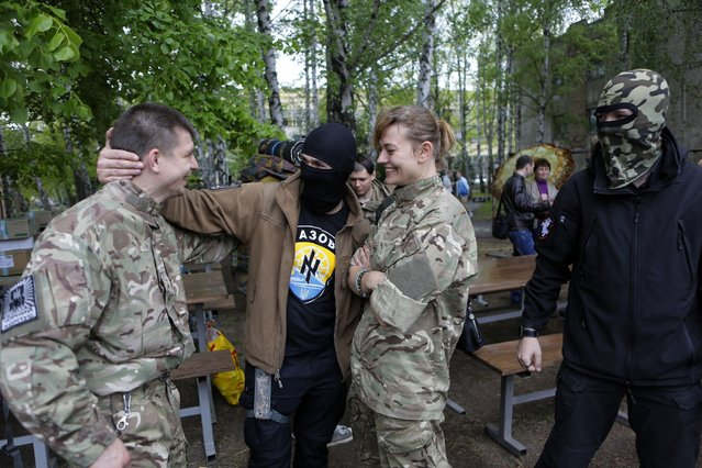 """Friends and relatives say goodbye to volunteers being sent to the eastern part of Ukraine to join the ranks of special battalion """"Azov"""" fighting against pro-Russian separatists, in Kiev, Ukraine, Thursday, May 7, 2015. Five Ukrainian government troops battling separatist forces in the east have been killed in one of the worst single days of bloodshed since a cease-fire was declared in February, military officials said Wednesday. (Photo by Sergei Chuzavkov/AP Photo)"""