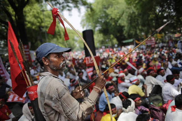 An Indian farmer holds a bow and an arrow as he attends a gathering near the Indian parliament for a protest against the Land Acquisition Bill, in New Delhi, India, Tuesday, May 5, 2015. Indian farmers protested against the ruling Bharatiya Janata Party's Land Acquisition Bill, calling it anti-farmer in a country where agriculture is the main livelihood for more than 60 percent of the 1.2 billion people. (Photo by Altaf Qadri/AP Photo)