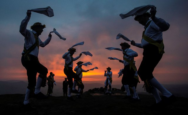Members of the Chapel-en-le-Frith Morris Dancers dance atop the Eccles Pike at High Peak in Derbyshire before sunrise on May 1, 2018. The Chapel-en-le-Frith dancers perform an annual dance atop the Eccles Pike at sunrise, as part of the ancient Celtic festival Beltane, celebrated on May Day or the beginning of summer. (Photo by Lindsey Parnaby/AFP Photo)