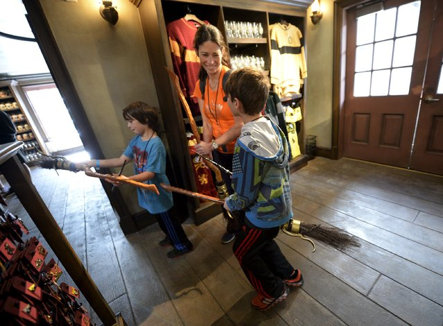 """Dove Rudman (C) and her children, Wyatt (L) and Cody try out witch brooms for sale inside Dervish and Banges general store in Hogsmeade Village during a soft opening and media tour of """"The Wizarding World of Harry Potter"""" theme park at the Universal Studios Hollywood in Los Angeles, California in this picture taken March 22, 2016. (Photo by Kevork Djansezian/Reuters)"""