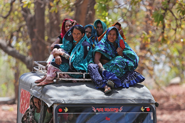 Women sit on top of a vehicle as they leave after casting their votes outside a polling station at Sirohi district in the desert Indian state of Rajasthan, India on April 29, 2019. (Photo by Amit Dave/Reuters)