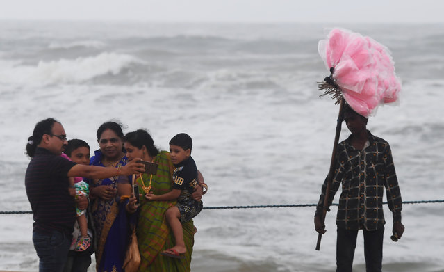 An Indian family takes a sefie next to a candy seller in a closed beach in Puri in the eastern Indian state of Odisha on May 2, 2019, as cyclone Fani approaches the Indian coastline. Nearly 800,000 people in eastern India have been evacuated ahead of a major cyclone packing winds gusting up to 200 kilometres (125 miles) per hour and torrential rains, officials said on May 2. (Photo by Dibyangshu Sarkar/AFP Photo)