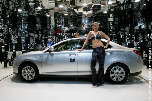 Models pose beside the world premiere display of the Roewe 550 during a special media opening of the Auto China 2008 show