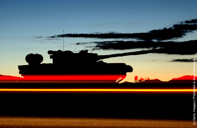 Morning commuter tail lights streak past a tank on display at the entrance to the U.S. Armys Fort Irwin Military Reserve