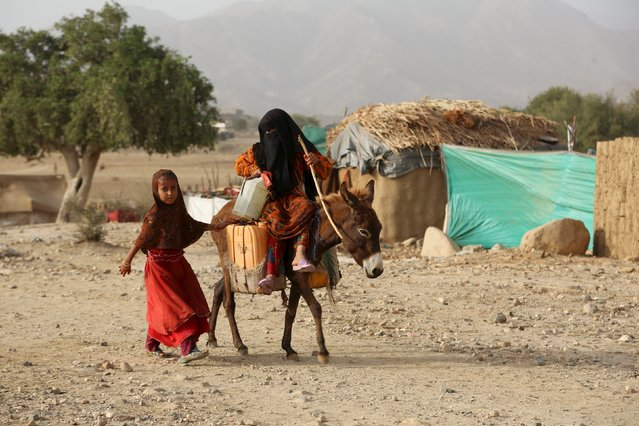 A girl rides a donkey as another walks by at the Shawqaba camp for internally displaced people who were forced to leave their villages by the war in Yemen's northwestern province of Hajjah March 12, 2016. In northwest Yemen, one of the poorest countries in the Middle East, about 400 families uprooted by the war have been stuck in the Shawqaba camp in Hajjah province for the past year. Residents live in poorly built huts that protect them neither from summer heat nor winter cold in a camp that lacks the most basic services. (Photo by Abduljabbar Zeyad/Reuters)