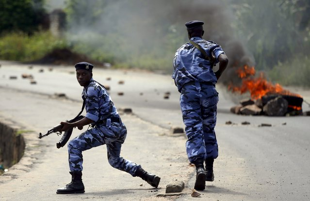 A policeman runs after protesters near a burning barricade during a protest against Burundi President Pierre Nkurunziza and his bid for a third term in Bujumbura, Burundi, May 21, 2015. (Photo by Goran Tomasevic/Reuters)