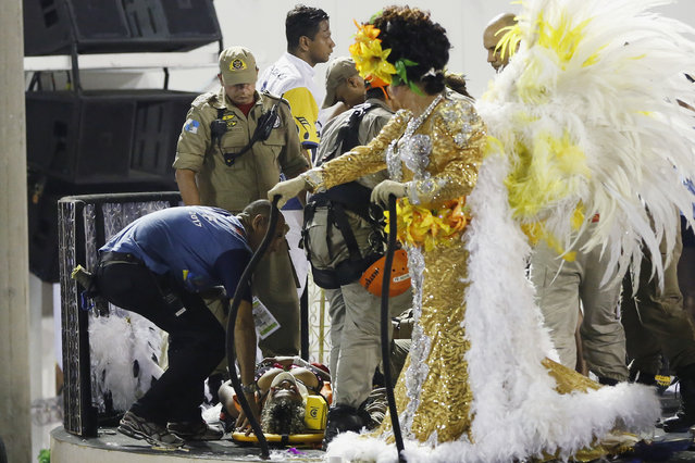 An injured person lies on a stretcher on the top of a float as she is being rescued during the performing of the Unidos da Tijuca samba school for the Carnival celebrations at the Sambadrome in Rio de Janeiro, Brazil, Tuesday, February 28, 2017. (Photo by Leo Correa/AP Photo)