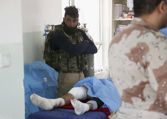 A Federal policeman, injured during fighting between Iraqi security forces and Islamic State militants, receives first aid in a field clinic on the western side of Mosul, Iraq, Monday, February 27, 2017. (Photo by Khalid Mohammed/AP Photo)