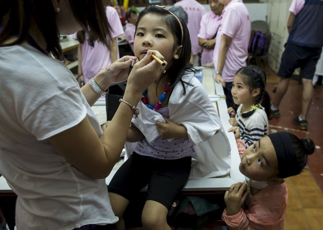 Phoebe Lo (L), a four-year-old, receives make up as Peony Chu (bottom R), a five-year-old, looks on before taking part in a Bun Festival parade at Hong Kong's Cheung Chau island, China May 25, 2015. (Photo by Tyrone Siu/Reuters)