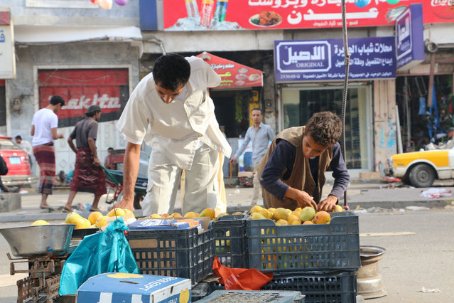 A Yemen boy, right, sells fruits on a street in Taiz city, Yemen, Sunday, May 17, 2015. (Photo by Abdulnasser Alseddik/AP Photo)