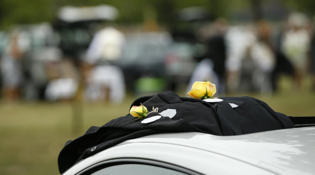Yellow roses adorn two button holes of gentlemen's morning suits resting on a sports cars in the No.1 car park on the second day of  Royal Ascot horse racing meet at Ascot, England, Wednesday, June 17, 2015. Royal Ascot is the annual five day horse race meeting that Britain's Queen Elizabeth II attends every day of the event.(AP Photo/Alastair Grant)