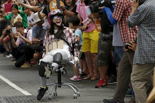 A competitor laughs while taking part in the office chair race ISU-1 Grand Prix in Tainan, southern Taiwan April 24, 2016. (Photo by Tyrone Siu/Reuters)