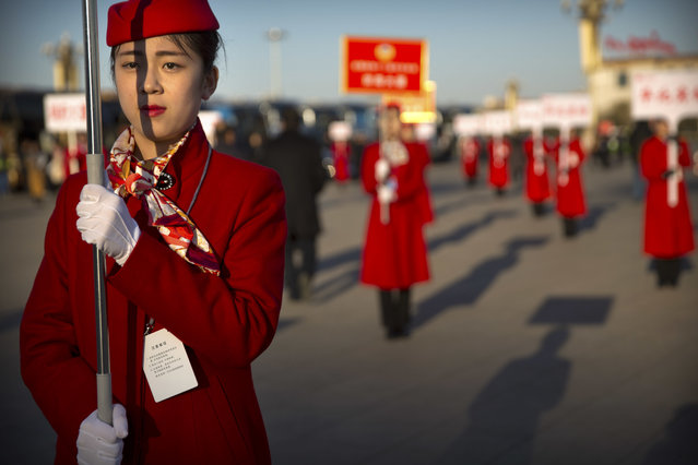 Hospitality staff hold signs to guide delegates as they leave following a plenary session of the Chinese People's Political Consultative Conference (CPPCC) at the Great Hall of the People in Beijing, Thursday, March 9, 2017. China's top leadership as well as thousands of delegates from around the country are gathered at the Chinese capital for the annual legislature meetings. (Photo by Mark Schiefelbein/AP Photo)