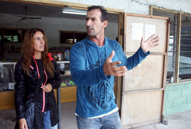 Joao Goncalves, a surfer and hotel owner from the Portuguese town of Peniche, gestures as he stands next to his partner Catarina Sa Nogueira outside a local shop on Kiritimati Island, part of the Pacific Island nation of Kiribati, April 5, 2016. (Photo by Lincoln Feast/Reuters)