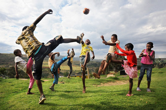 High in the mountains, a group of children play with a homemade soccer ball. Quthing, Lesotho. (Photo by David Lazar/Smithsonian.com)