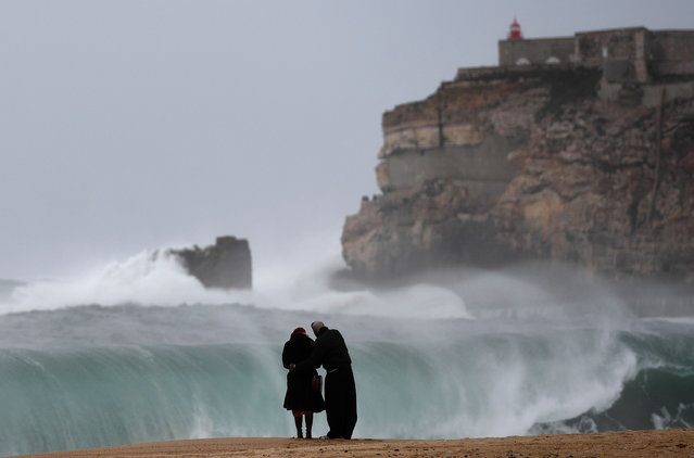 A couple stands on the beach as big waves break near the Sao Miguel Arcanjo fort in Nazare, central Portugal, on February 2, 2017. (Photo by Francisco Leong/AFP Photo)