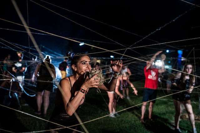Crossed strings are rolled up by participants during the performance entitled It's Not That Way, It's This Way by the South Korean-French group Galmae at the Sziget (Island) Festival on Shipyard Island, Northern Budapest, Hungary, 12 August 2019. The festival is one of the biggest cultural events of Europe offering art exhibitions, theatrical and circus performances and above all music concerts in seven days. (Photo by Marton Monus/EPA/EFE)