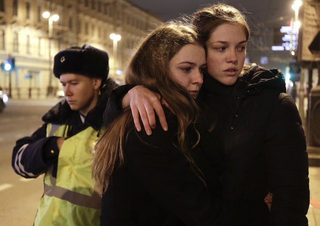 Women grieve near the Tekhnologichesky Institut subway station in St.Petersburg, Russia, Monday, April 3, 2017. A bomb blast tore through a subway train deep under Russia's second-largest city Monday, killing several people and wounding many more in a chaotic scene that left victims sprawled on a smoky platform. (Photo by Dmitri Lovetsky/AP Photo)
