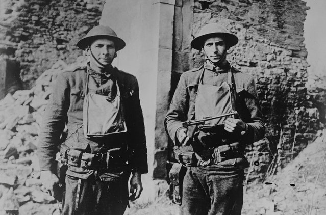 Two American soldiers, Corporal Howard Thompson and James H. White, who were part of a group that killed and captured several Germans in no man's land. Thompson holds a pistol taken from a German soldier killed by White. Photograph taken in Ancerviller, France, March 11, 1918. (Photo by Reuters/Courtesy Library of Congress)