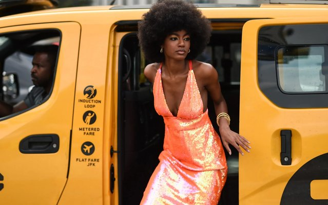 A guest is seen wearing an orange shiny dress outside the Area show during New York Fashion Week S/S20 on September 07, 2019 in New York City. (Photo by Daniel Zuchnik/Getty Images)