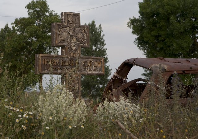 An abandoned car is seen near a cross in the village of Tbeti near Tskhinvali, the capital of the breakaway region of South Ossetia, Georgia, July 4, 2015. (Photo by Kazbek Basaev/Reuters)