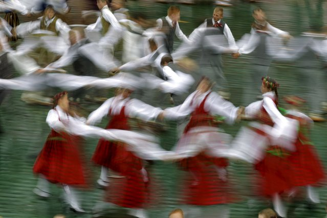 Dancers wear traditional dress as they perform during a student's song and dance festival in Riga, Latvia, July 10, 2015. (Photo by Ints Kalnins/Reuters)