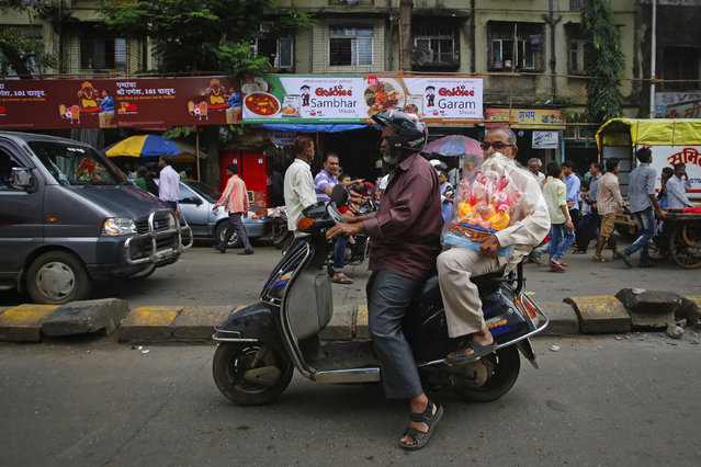 Devotees carry a statue of the Hindu god Ganesh, the deity of prosperity, on a scooter on the first day of the ten-day-long Ganesh Chaturthi festival in Mumbai September 9, 2013. (Photo by Danish Siddiqui/Reuters)