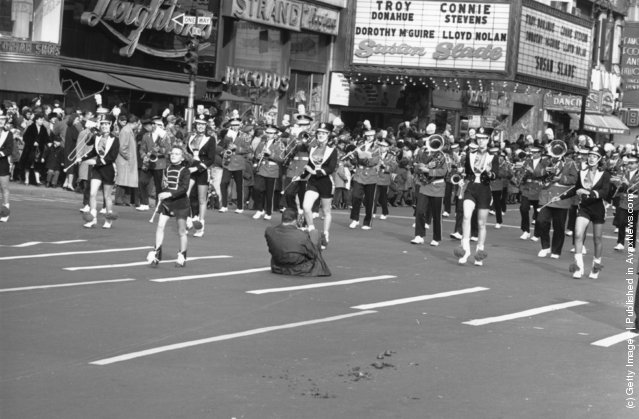 A man squats in the street to photograph a brass band and majorettes marching in the Thanksgiving Parade near Times Square, New York, 1961