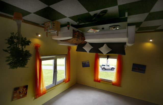 """A car is seen through the living room window of the """"Crazy House"""", which is completely built upside-down, in the village of Affoldern near the Edersee lake, May 7, 2014. Three friends came up with the idea to build the tourist attraction, which cost about 200,000 euros and took some six weeks to complete. (Photo by Kai Pfaffenbach/Reuters)"""