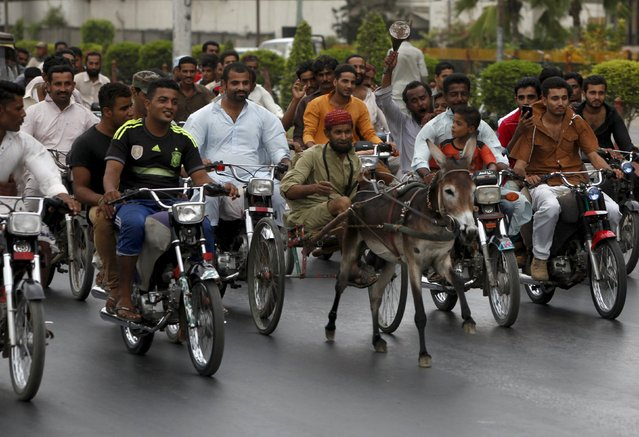 Men on motor cycles keep track as a man rides his donkey cart during a race through Karachi, Pakistan, July 5, 2015. (Photo by Akhtar Soomro/Reuters)