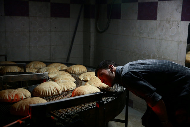 A man inspects a line of bread to be distributed as aid in the rebel held besieged city of Douma, in the eastern Damascus suburb of Ghouta, Syria April 15, 2017. Picture taken April 15, 2017. The bakery was reopened by the Unified Aid Office, which is in charge of distributing aid in eastern Ghouta, to alleviate the impact of a rise in bread prices to $2 per kg, according to the men running the bakery. (Photo by Bassam Khabieh/Reuters)
