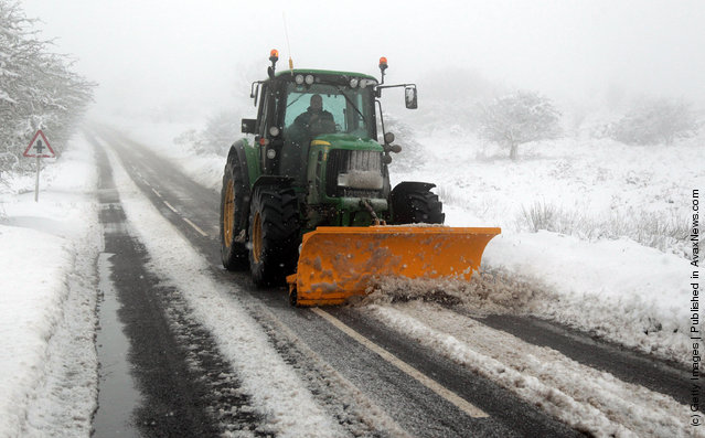 A tractor with a snow plough clears snow off the road near Dulverton