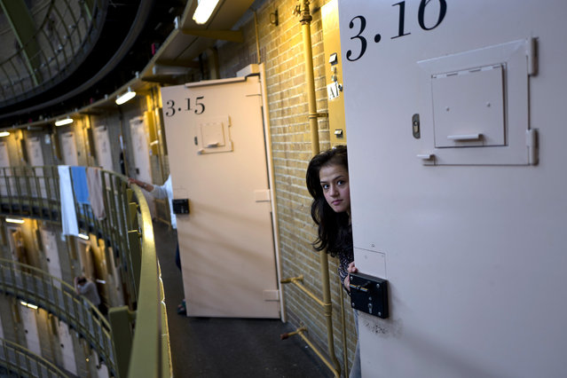 In this Saturday, May 7, 2016 photo, Afghan refugee Shazia Lutfi, 19, peeks through the door of her room at the former prison of De Koepel in Haarlem, Netherlands. The government has let Belgium and Norway put prisoners in its empty cells and now, amid the huge flow of migrants into Europe, several Dutch prisons have been temporarily pressed into service as asylum seeker centers. (Photo by Muhammed Muheisen/AP Photo)