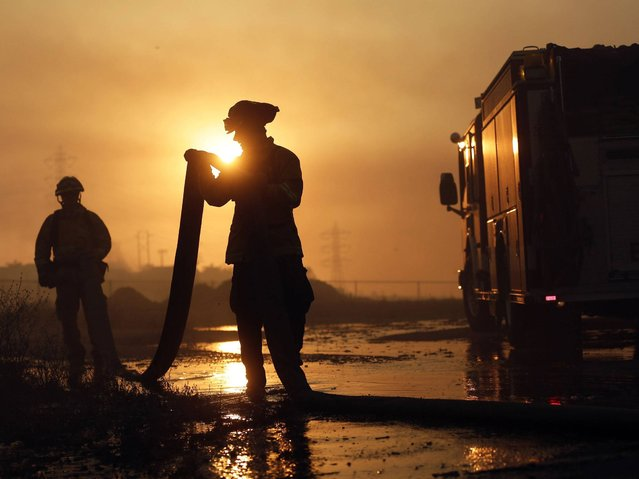 Del Mar firefighters roll up hose after a day fighting wildfires Wednesday, May 14, 2014, in Carlsbad, Calif. More wildfires broke out Wednesday in San Diego County, threatening homes in Carlsbad and forcing the evacuations of military housing and an elementary school at Camp Pendleton. (Photo by AP Photo)