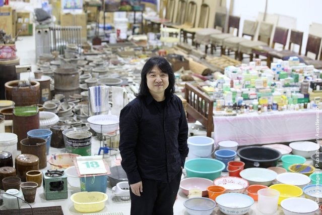 "Chinese artist Song Dong stands in his installation entitled ""Waste Not"" in The Curve at the Barbican Art Gallery"