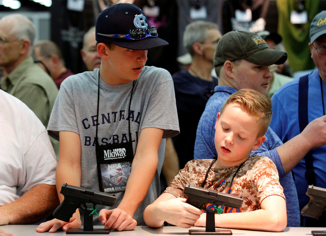 Gun enthusiasts look over guns at FN America firearms at the National Rifle Association's annual meetings and exhibits show in Louisville, Kentucky, May 21, 2016. (Photo by John Sommers II/Reuters)