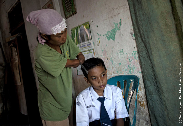 Armless professional photographer Rusidah, 44, combs her twelve-year-old son Nugraha's hair