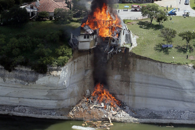 Smoke rises from a house deliberately set on fire, days after part of the ground it was resting on collapsed into Lake Whitney, Texas June 13, 2014. Building crews set fire on Friday to the luxury lake house left dangling about 75 feet (23 meters) on a decaying cliff that has been giving way underneath the structure. (Photo by Brandon Wade/Reuters)