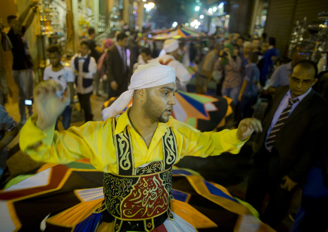 In this Sunday, June 5, 2016 photo, whirling dervishes spin during a performance to mark the holy month of Ramadan at El-Moez Street in historical Fatimid Cairo, Egypt. Devout Muslims began to celebrate Ramadan, the holiest month in the Islamic calendar, refraining from eating, drinking, smoking and s*x from sunrise to sunset. (Photo by Amr Nabil/AP Photo)