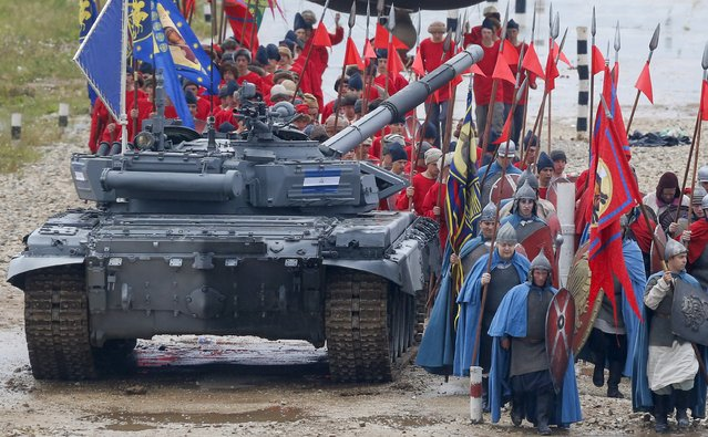Participants dressed as Old Russian knights walk past a tank during an opening ceremony of the International Army Games-2015 in Alabino, outside Moscow, Russia, August 1, 2015. (Photo by Maxim Shemetov/Reuters)