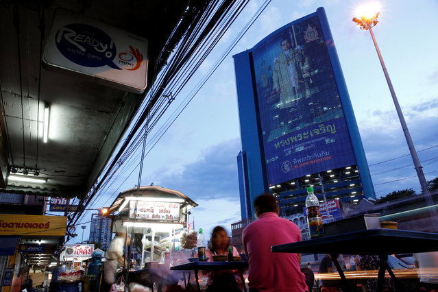 People have dinner on a street in front of a building with a picture of Thailand's King Bhumibol Adulyadej in Bangkok, Thailand, June 7, 2016. (Photo by Athit Perawongmetha/Reuters)