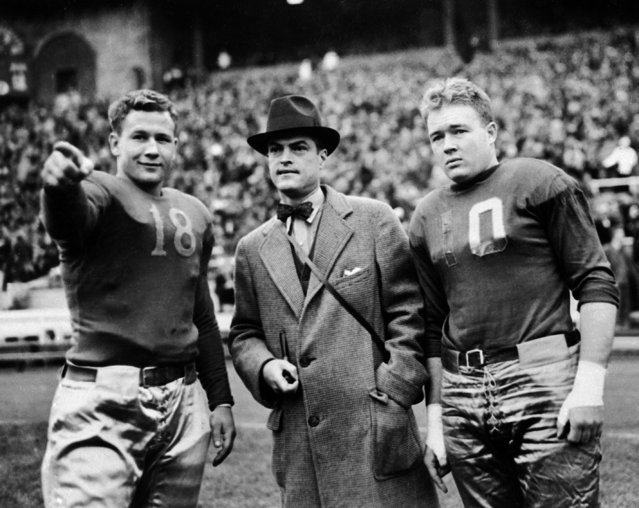 In this October 10, 1936, file photo, Ohio State team captain Merle Wendt, left, points out to Alan Gould, center, Associated Press sports editor, and Pittsbugh captain Bill Glassford, where he intends to cross Pitt's goal line before their game in Columbus, Ohio. The one constant in college football over the last 80 years has been the AP poll. Before the AP started asking its member sports writers and editors to vote for the top teams, then-sports editor Alan J. Gould in 1935 went about ranking them himself. (Photo by Harry Hall/AP Photo)