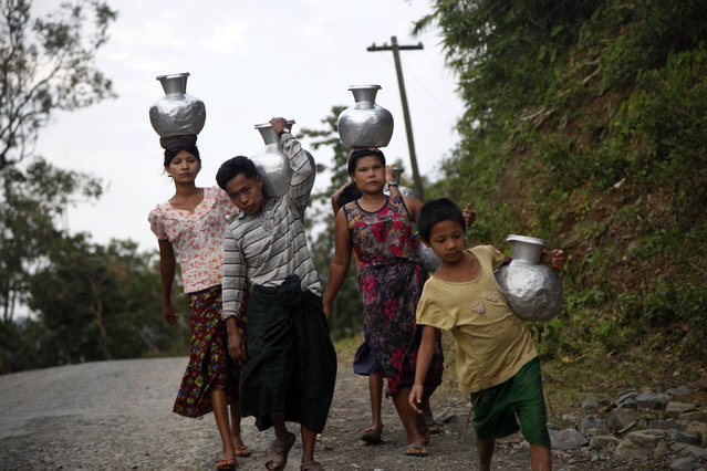 Local residents carry containers  to fetch water at a well in Myauk U, Rakhine State, western Myanmar, Tuesday, August 4, 2015. (Photo by Khin Maung Win/AP Photo)