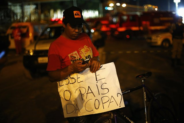 """A man holds a banner that reads """"This is the country of the cup?"""" next to a bridge that collapsed while under construction in Belo Horizonte, July  3, 2014. The unfinished overpass collapsed in the Brazilian World Cup host city of Belo Horizonte on Thursday, killing at least one person and casting a shadow over a tournament that has suffered repeated construction accidents and delays. (Photo by Ivan Alvarado/Reuters)"""