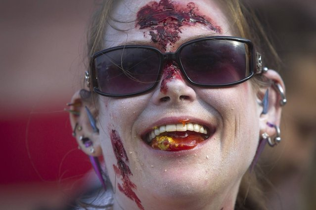 """Molly Schuyler, dressed as a zombie, smiles after winning the brain eating contest during the """"Zombie Takeover of Coney Island"""" in Coney Island in the Brooklyn borough of New York, July 2, 2014. Schuyler ate 5.5 lbs (2.5 kg) of pig brains to set a new record according to organizers. (Photo by Carlo Allegri/Reuters)"""