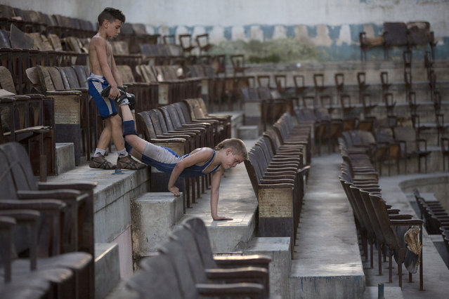 Jonatan Leliebre, 10 (L), and Oscar Torres, 9, exercise before a wrestling practice session at an old Basque ball gymnasium in downtown Havana, October 30, 2014. (Photo by Alexandre Meneghini/Reuters)