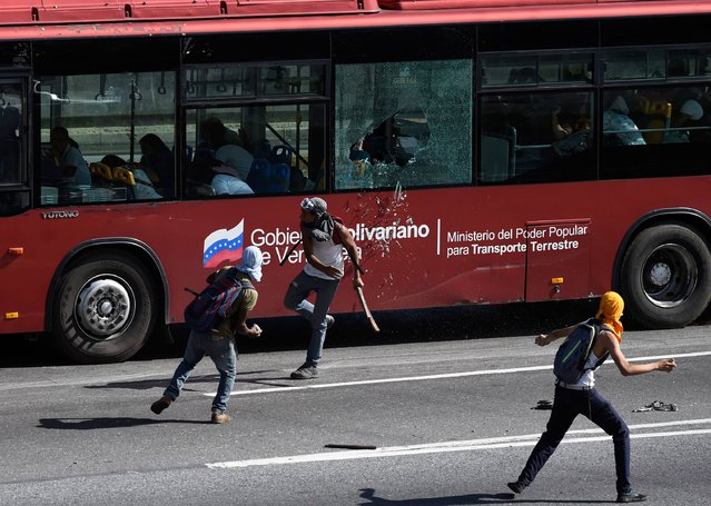 Protesters throw stones at a public transport bus during a demonstration against the government of President Nicolas Maduro, in Caracas on July 4, 2017. A political and economic crisis in the oil-producing country has spawned often violent demonstrations by protesters demanding Maduro's resignation and new elections. The unrest has left 90 people dead since April 1. (Photo by Juan Barreto/AFP Photo)