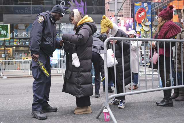 Police officers check people bags before they enter Times Square in New York on New Year's Eve, Tuesday, December 31, 2019. (Photo by Seth Wenig/AP Photo)