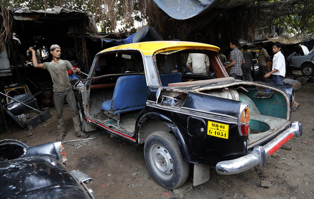 In this Wednesday, March 26, 2014 photo, a worker dismantles a taxi at a junk yard in Mumbai, India. The distinctive black-and-yellow licensed cabs number just 42,000 in Mumbai, inadequate for a city of 22 million. Taxi-hailing smartphone app Uber is making a big push into Asia with the company starting operations in 18 cities in Asia and the South Pacific including Seoul, Shanghai, Bangkok, Hong Kong and five Indian cities in the last year. (Photo by Rajanish Kakade/AP Photo)